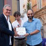 Fadi riceve il suo premio da Piero Ricci, presidente dell'ordine dei giornalisti di Puglia